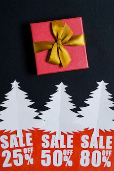 Paper christmas trees with red discount cards and a gift