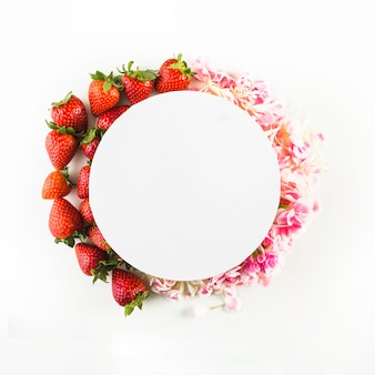 Paper circle on strawberries and petals