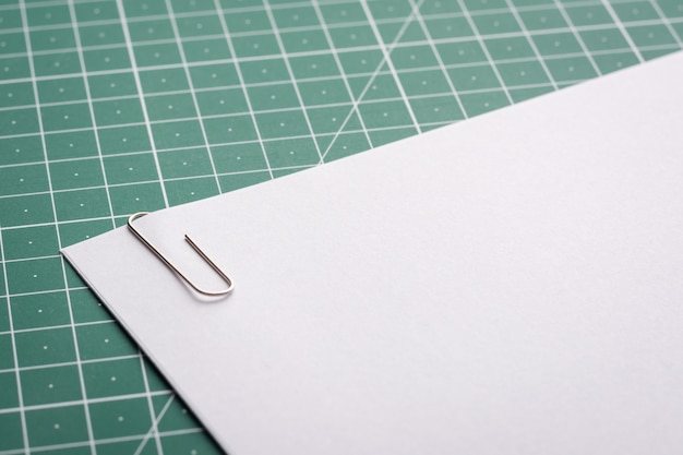 Paper clip on stack of papers lying on cutting mat