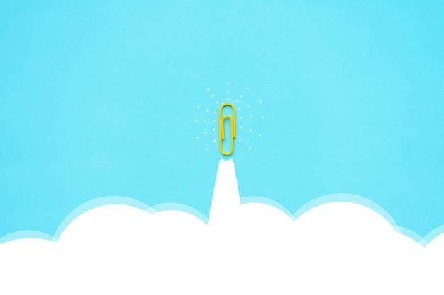 空の上を移動するペーパークリップ黄色創造的なアイデアと革新の概念は刺激します