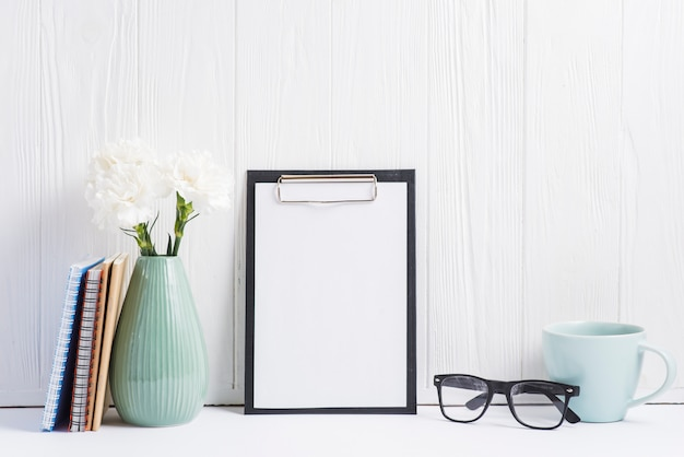 Paper on clipboard; vase; eyeglasses; cup; books and vase on white backdrop