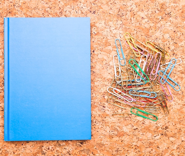 Paper clips and blue notebook on cork board