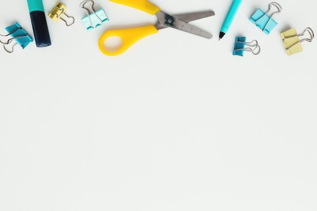 Paper clips, marker and pencil, scissors on white background. work and education concept.