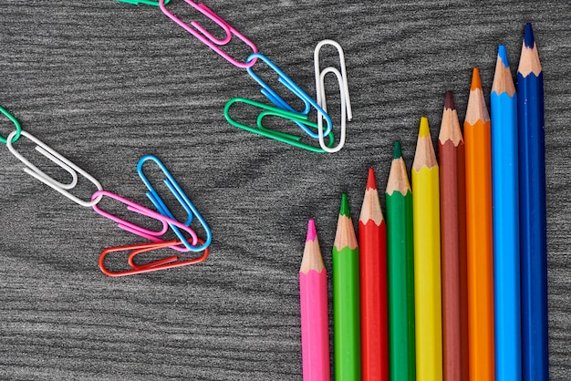 Paper clips pointing at color crayons
