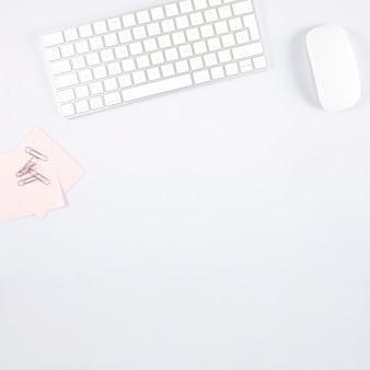 Paper clips and sticky notes near keyboard and mouse