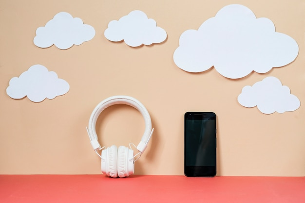 Paper clouds near smartphone and headphones