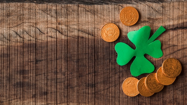 Paper clover and golden coins on board