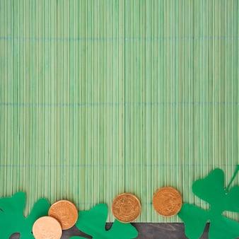 Paper clovers near coins on bamboo mat