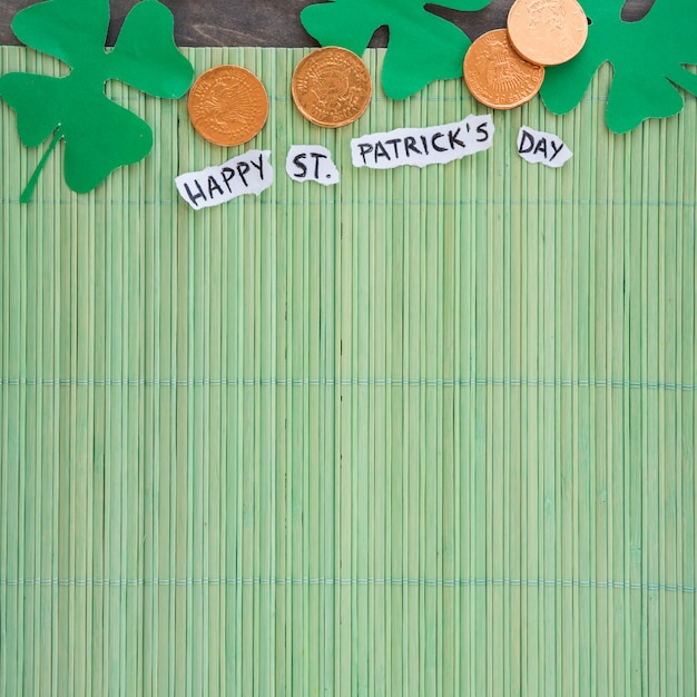 Paper clovers near coins and happy st patricks day title on bamboo mat
