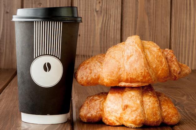 종이 커피 컵과 크루아상 나무 배경, 복사 공간.