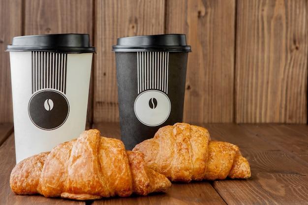木製の背景に紙のコーヒーカップとクロワッサン、コピースペース。