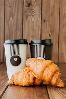 Бумажная кофейная чашка и круассаны на деревянной стене, копией пространства.