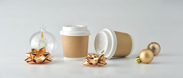 Paper coffee cup and coffee beans on white background.