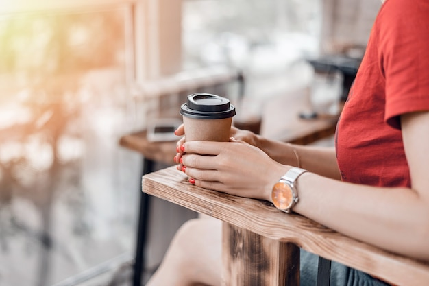 Paper coffee cup to go in woman's hands with red manicure while sitting in cafe.