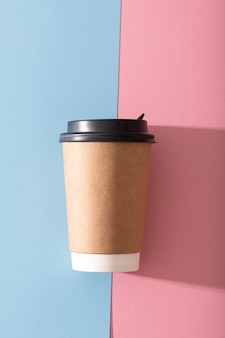 パステルピンクの背景に紙のコーヒーカップ