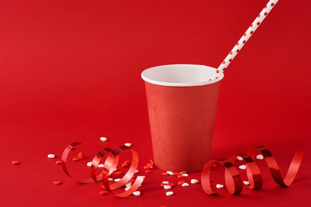 Paper coffee cup with festive decorations and confetti on red backgrond