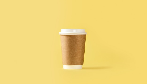 Paper coffee cup with white lid on yellow background