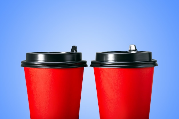 Paper coffee cups on blue background.