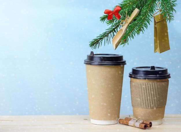 전나무 나무에 크리스마스 장식과 함께 나무 테이블에 종이 커피 컵. 크리스마스 커피 배경