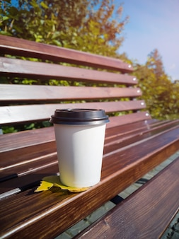 A paper coffee mug stands on a wooden bench in the park on a sunny day.