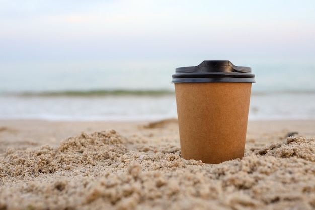 Paper coffee mugs laying on the sandy beach in summer.