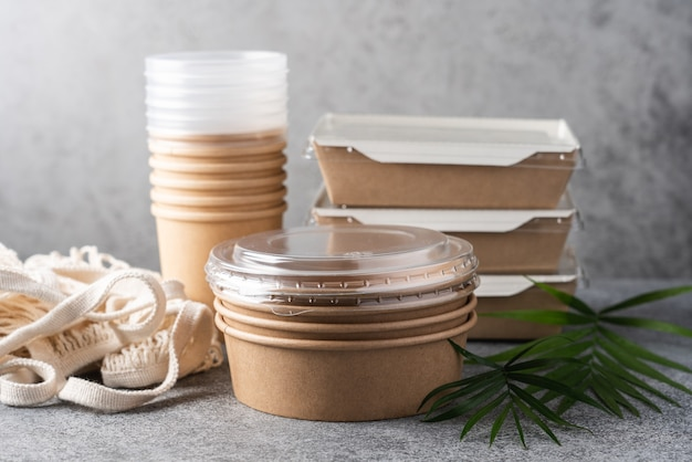 灰色の背景に葉を持つ食品配達用の紙容器