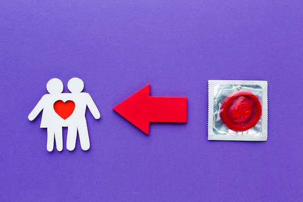 Paper couple next to red condom