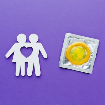 Paper couple next to yellow condom