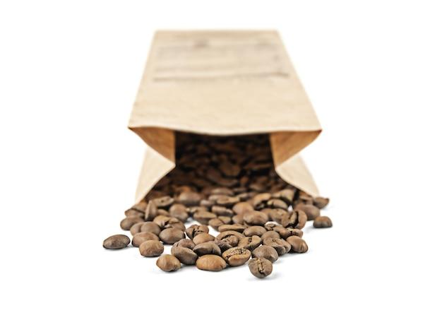 종이 공예 가방은 흰색 표면에 고립 된 볶은 커피 콩이 쏟아져있다.