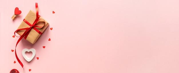 Бумажное ремесло подарочная коробка с красным бантом из ленты и красными сердцами. праздничная концепция на день святого валентина