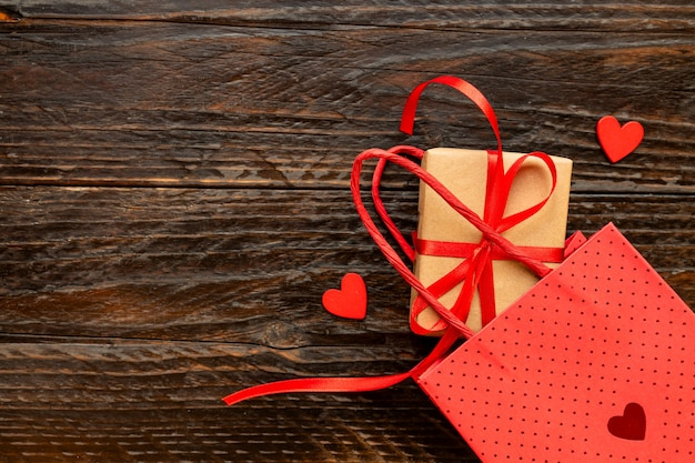 赤いリボンの弓、紙袋、赤いハートのペーパークラフトギフトボックス。バレンタインデー、母の日、誕生日のお祭りのコンセプト。