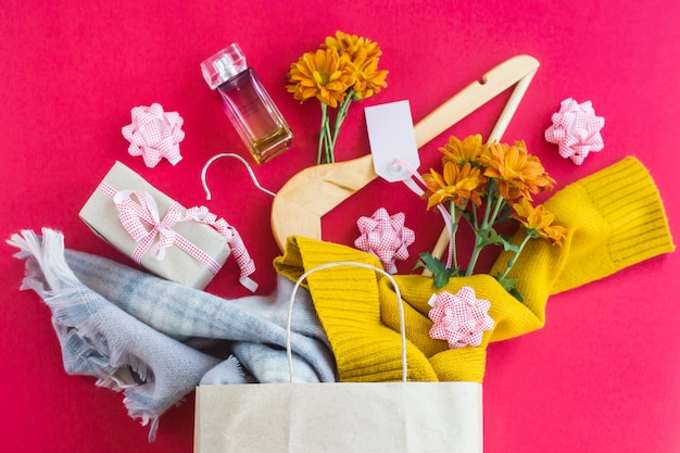 Paper craft package with women's purchases - clothes, gifts, perfumes, flowers