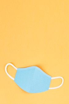 Paper craft surgical mask on a yellow background illustration