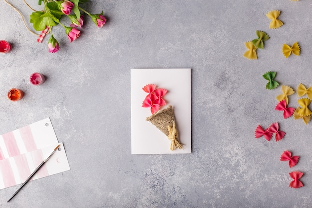 Paper crafts for mother day, 8 march or birthday. small child doing a bouquet of flowers out of colored paper and colored pasta.