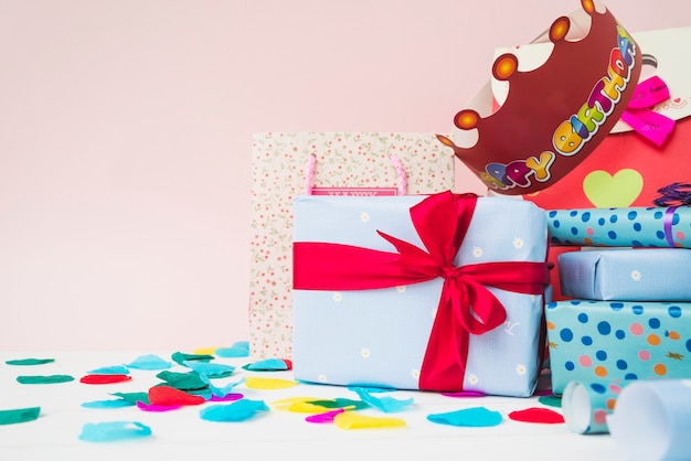 Paper crown over the present gift boxes on table against pink background