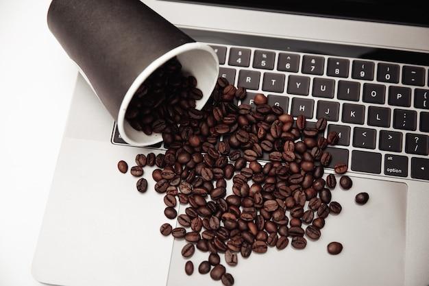 Бумажный стаканчик и кофейные зерна на клавиатуре на белом столе