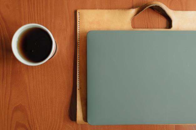 テーブルの上の紙コップとラップトップ。在宅勤務の概念。
