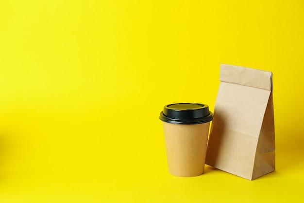 Бумажный стаканчик и бумажный пакет на желтой поверхности