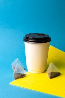 黄青色の背景に紙コップとティーバッグ