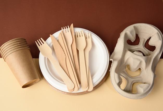 Бумажный стаканчик и деревянная вилка, пустая круглая одноразовая тарелка коричневого цвета из переработанных материалов на коричневой поверхности. концепция отсутствия неперерабатываемого мусора, отказ от пластика, вид сверху