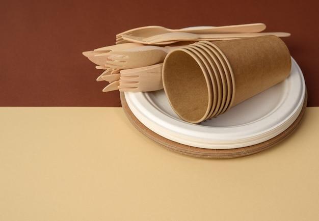 Бумажный стаканчик и деревянная вилка, пустая круглая одноразовая тарелка коричневого цвета из переработанных материалов на коричневой поверхности. концепция отсутствия неперерабатываемого мусора, отказ от пластика