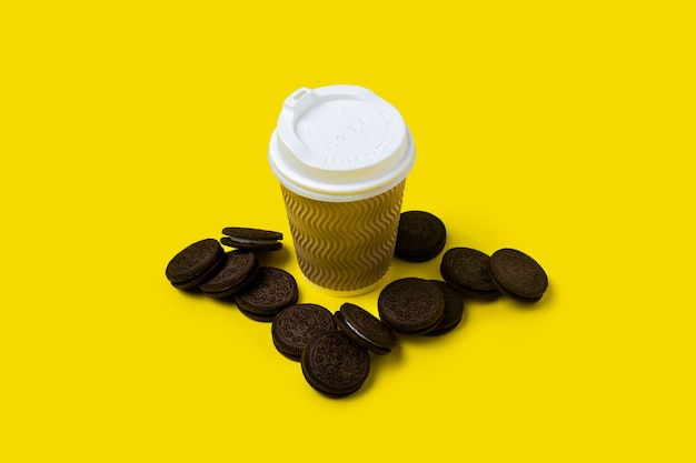 Paper cup and chocolate chip cookies on a yellow.