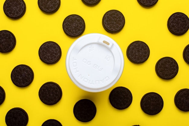 Paper cup and chocolate chip cookies on a yellow