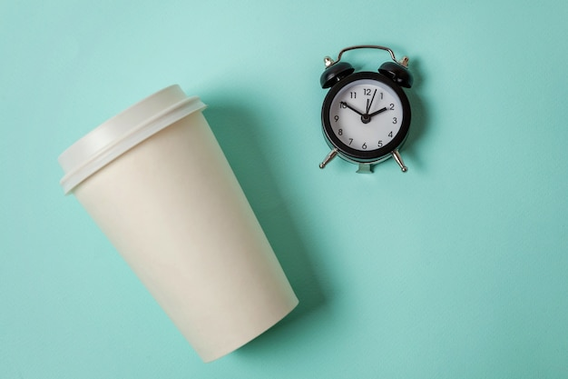 Paper cup of coffee and alarm clock