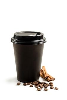 Бумажный стаканчик, кофейные зерна и палочки корицы на белом фоне с копией пространства.