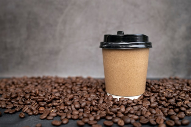 Paper cup of coffee and beans on black wooden floor background