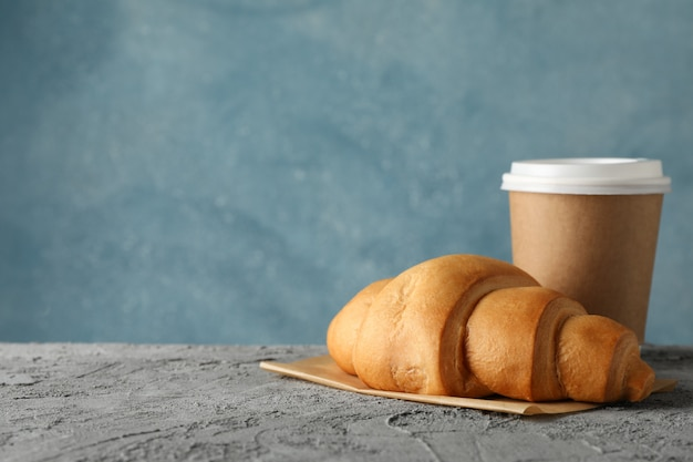 Paper cup of coffee and croissant on grey table, space for text