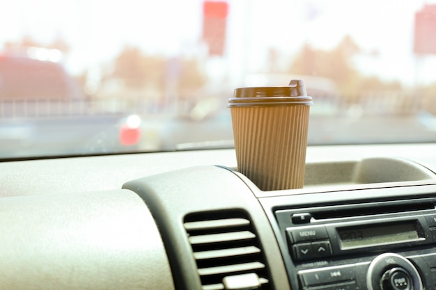 A paper cup of coffee on dashboard in the car.