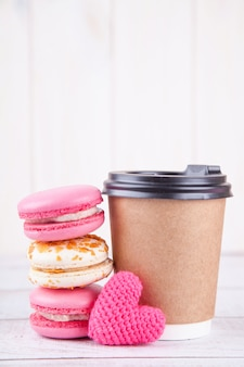 Paper cup of coffee, macarons and knitted pink heart