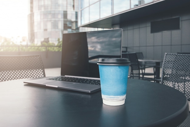 Paper cup of coffee and open laptop on table of street cafe in business district of city